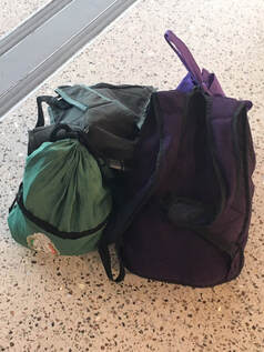 Photo of two small backpacks and a shoe bag.